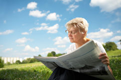 Reading in park. The woman in old age sits on a grass in park on a background of the blue sky and reads the newspaper Royalty Free Stock Photo