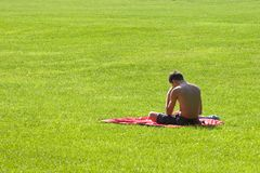Reading in the Park_8241-1S. Man Alone Reading in the Park on a Sunny Day stock images