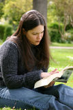 Reading in the park. A woman sits reading in the park Royalty Free Stock Images