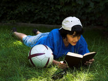 Reading in the park. Boy reading in the park, next to his football Royalty Free Stock Photos