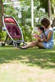 Reading in the park. Chinese women reading a book to her daughter while sitting in the park Royalty Free Stock Photo