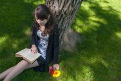 Reading in the park. Cute girl sitting on grass and read an old book Stock Photo