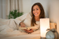 Reading Past Bedtime. Beautiful smiling girl relaxing in bed and reading book Stock Image