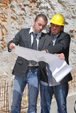 Reading plan. Two construction workers read paper Stock Images