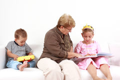 Reading and playing with granny Royalty Free Stock Images