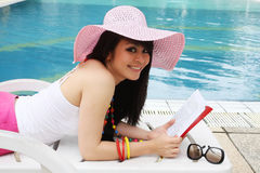 Reading at pool. Pretty woman reading book near the pool Royalty Free Stock Photo