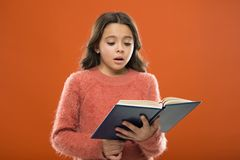 Reading practice for kids. Childrens literature. Girl hold book read story over orange background. Child enjoy reading