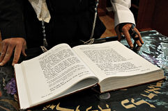 Reading from a prayer book. In a synagogue with the hands of the chazan (prayer leader Stock Photo
