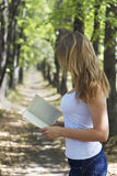 Reading in privat. Lady reading interesting book alone in sunny alley Royalty Free Stock Images