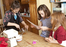 Reading the Recipe, Beating the Egg. Three young sisters are working together to make gingerbread for Christmas presents. The egg and syrup has to be beaten royalty free stock photo