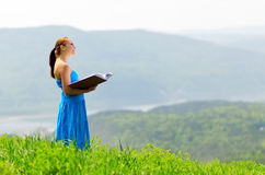 Red haired woman with book on the hilltop Stock Image