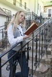 Reading and Relaxation Ideas. Portrait of Sensual Caucasian Blond Woman Reading Book Outdoors in City Stock Photos
