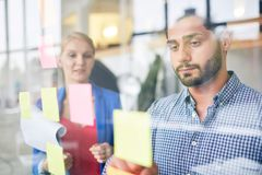Reading reminder. Businessman looking at one of notepapers on transparent office board with colleague near by Stock Photos
