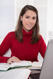 Reading and research: brunette woman sitting in red jumper at de. Sk with books and laptop - student - young girl Stock Image