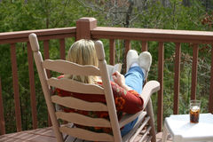 Reading and Resting. Lady relaxing while reading a book outside on a deck Stock Image