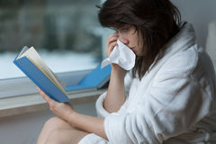 Reading the romance and crying. Sensitive young woman reading romance and crying Royalty Free Stock Photography
