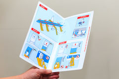 Reading about safety. Concept for airline safety. Hand holding safety instruction card found in the seatback pocket of  airliners Stock Image