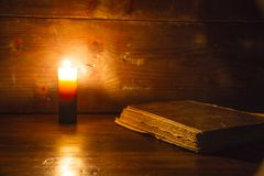 Reading scene in ancient times: an old book leaning on ruined wooden table lighted by a candle on a wooden background royalty free stock image