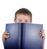 Reading School Boy with Book. A young school boy is holding a blue book on a white isolated background. His eyes are looking at the camera and he is reading Stock Photography