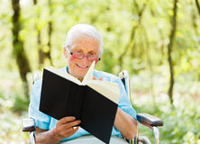 Reading Senior Lady. Kind elderly lady in wheelchair with book in hands reading story outdoors Stock Image