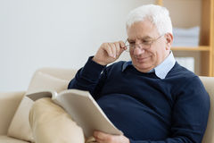 Reading senior. Senior man in glasses reading at home Royalty Free Stock Images