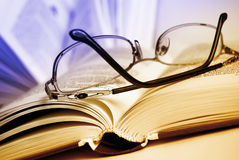 Reading set. Glasses and book, extreme close-up and toned by two colors Stock Photography