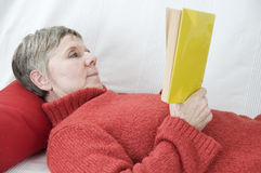 Reading on the settee bed side Stock Photo