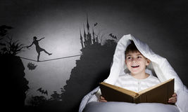 Reading before sleep. Little cute boy reading book in bed under blanket Royalty Free Stock Images