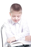 Reading with smile. Smiling kid in white reading book with crossed arms isolated Royalty Free Stock Photography