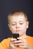 Reading SMS. Boy in orange shirt looking to mobile phone straight view Royalty Free Stock Photos