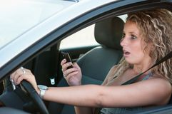 Reading SMS while driving car Royalty Free Stock Photography