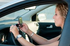 Reading SMS while driving car Royalty Free Stock Photo