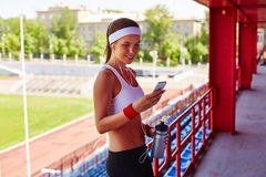 Reading sms at stadium. Happy girl with smartphone and earphones reading sms at stadium Stock Photography