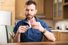 Reading some medicine labels. Portrait of a guy with a beard reading the back of some medicine blisters at home stock photography