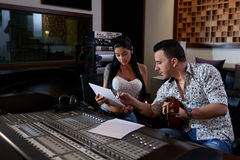 Reading song. Producer and pretty singer reading text of new song royalty free stock photography