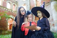 Reading spell. Little girls in witch attire reading halloween spell on paper Royalty Free Stock Image