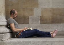Reading on the steps. Bare foot man reading on church steps Stock Photos