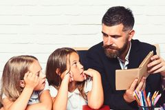 Reading a story. father read book to his daughters. royalty free stock image