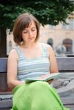 Reading on street. Young woman dresse�d in green reads book on bench in downtown Royalty Free Stock Image