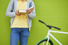 Reading students book. Student with bicycle standing against green wall and reading a book Royalty Free Stock Photo
