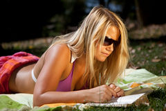 Reading in the sun. Young woman wearing sunglasses is reading a book in the sun Royalty Free Stock Photo