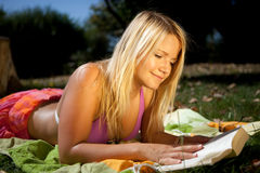 Reading in the sun. Young happy woman is reading a book in the sun Royalty Free Stock Images