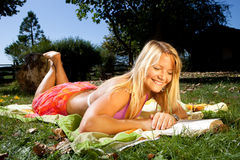 Reading in the sun. Young happy woman is reading a book in the sun Royalty Free Stock Photography