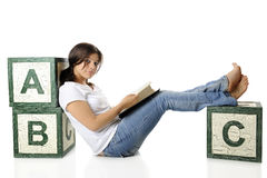 Reading Supported by ABCs. An attractive young teen looking up from and old book she's reading while supported by large antique alphabet blocks.  Isolated on Stock Photography