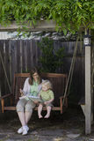 Reading in a Swing. A mother and her two-year old son enjoy reading a book together while sitting on a swing in an arbor. Room around image for text Stock Photography