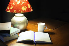 A table lamp, a white cup, an open book, some books, on a brown table Royalty Free Stock Photos
