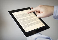 Reading on a tablet Royalty Free Stock Images