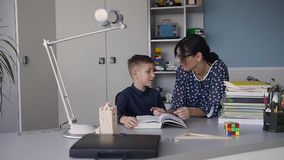 Reading with teacher - an elementary school boy reads aloud to her teacher. Teacher sitting at desk next to male student. A little guy with his young mother in stock footage
