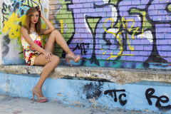 Fashion shooting. Girl next to a graffiti wall Stock Image