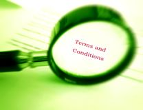 Reading terms and conditions. Concept image of a magnifier used to focus on the words Terms and conditions in a contract document. Simple composition with copy